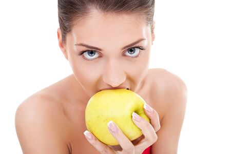 Sexy woman about to bite into an apple on a white background photo