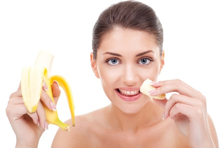 Picture of young woman eating banana and smiling photo
