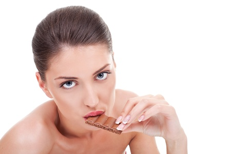 woman bar: Shot of a beautiful young woman holding  and eating chocolate bar