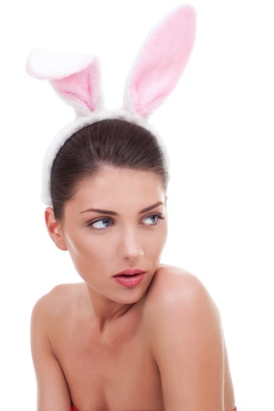beautiful young woman wearing cute bunny ears looking to her side, over white photo