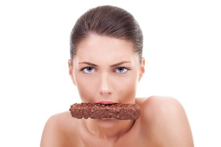 craving: Portrait of young serious woman eating chocolate bar over white