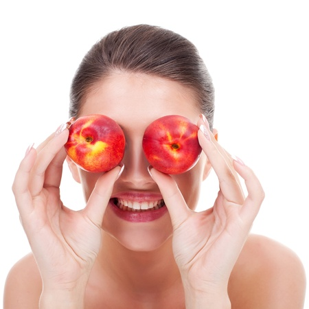 over eating: Young happy woman with red peaches over her eyes on white background Stock Photo
