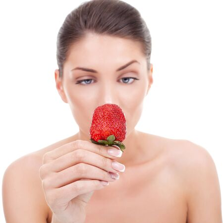 Portrait of young woman with bare shoulders holding ripe strawberry  photo