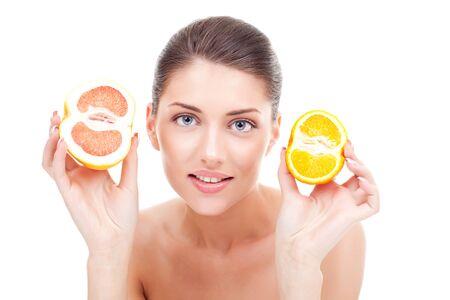 beautiful woman choosing between a grapefruit and an orange photo