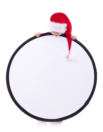 Child in a Christmas hat and and looking to a big blank sign over white photo