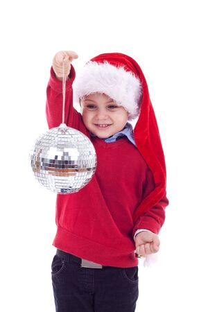 Small boy in Santa's red hat holding a glass disco ball over white  photo