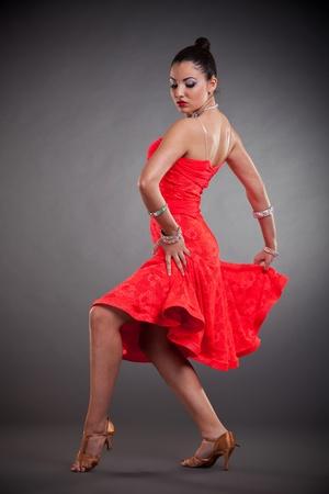 sexy latino dancer in a sensual dance pose over dark background photo