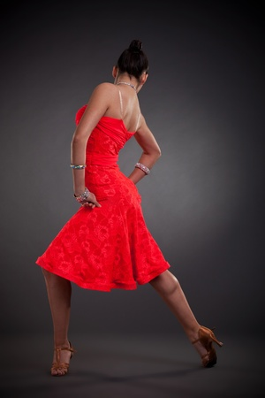 back of a sexy latino dancer posing on dark background photo