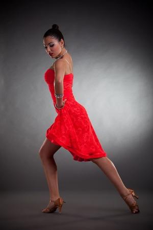 latino woman dancer posing on a dark studio background photo