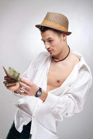 young player counting his winnings in front of a studio background photo
