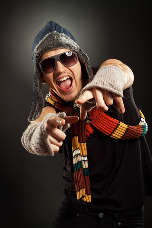 excited young man in a nice fur hat and gloves, pointing to you Stock Photo - 10933786