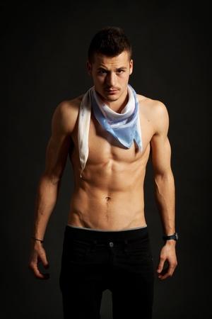 hombre sin camisa: Hombre sexy muscular con un pañuelo sobre fondo oscuro