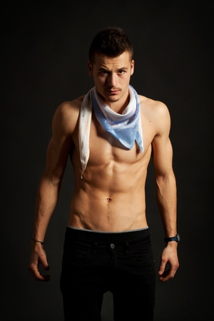 Sexy muscular man wearing a scarf over dark background  Stock Photo - 10933705