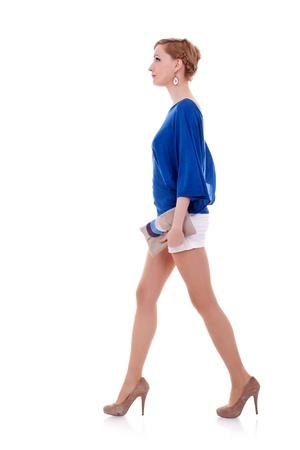 jeune femme confiante est la marche. Elle est souriant et en regardant loin de la caméra isolée sur fond blanc
