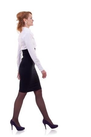 jeune femme d'affaires est la marche. Elle est souriant et en regardant loin de la caméra isolée sur fond blanc Banque d'images
