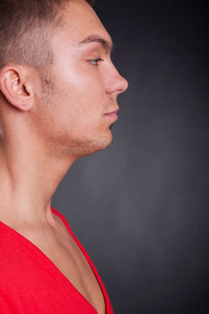 side view of a young casual man on dark background Stock Photo - 10933815