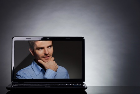 reflective background: casual business man on the screen of a laptop, on reflective table   Stock Photo