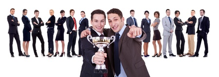 winning businessteam with two leaders, one holding a trophy, one pointing to you! photo