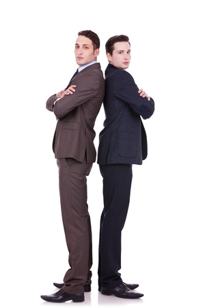 full body picture of two serious business men standing back to back over white background Stock Photo - 11187711