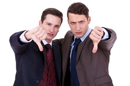 thumbs down: two young business men with thumb down gesture on white background