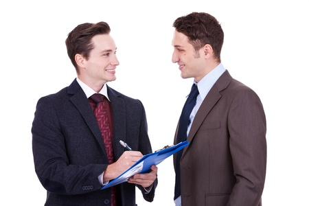 Two business people standing working in team together and discussing the problem looking into clipboard Stock Photo - 11188285