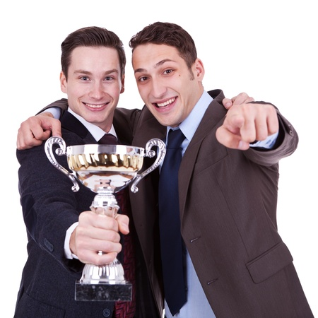 first place: two young winning business men pointing to you, over white background