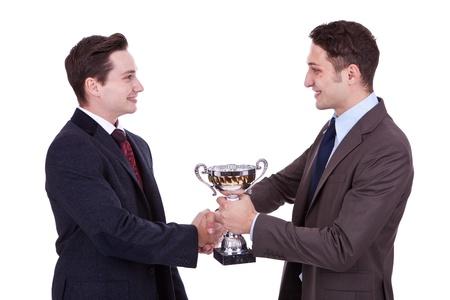 primer lugar: hombre de negocios entrega un trofeo a su coleague ganar y apret�n de manos le