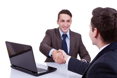 young business men reaching to an agreement at their desk, against white background photo