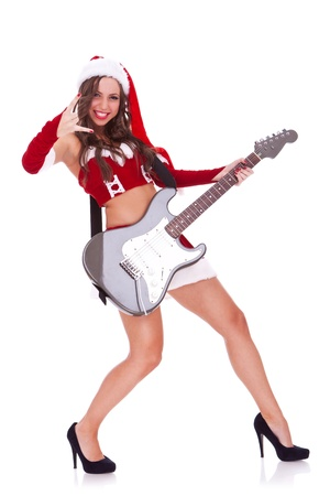 passionate santa woman playing an electric guitar on white background photo