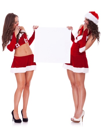 two sexy santa women holding and looking to a blank board on white background photo