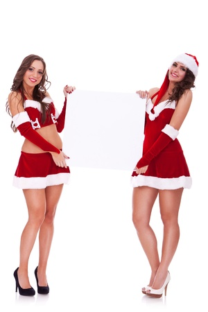 two sexy santa women holding  a blank board on white background photo