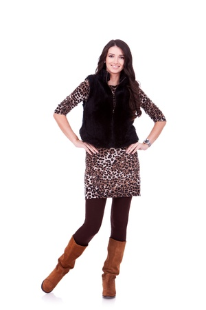 nice young woman standing with her hands on hips, and wearing fur coat Stock Photo