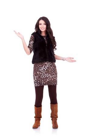 young woman in fur coat welcoming you, over white background photo