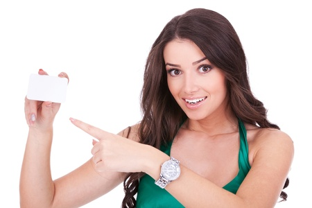 Portrait of a smiling young woman pointing at blank card in her hand against white background  photo