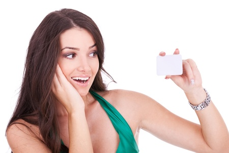 Portrait of an excited young woman looking at her bussiness card against white background  photo