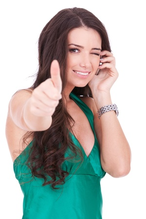 winking: casual woman talking by cell phone making OK sign and winking