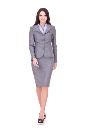 skirt suit: Business woman walking in full length on white background