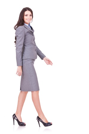 skirt suit: side view of a business woman walking in full length on white background Stock Photo