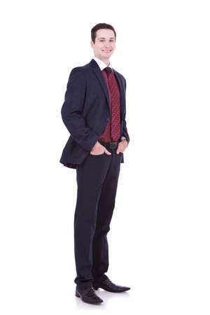 Full length of a handsome business man standing with hands in pocket against white  photo