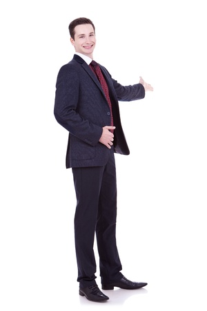 Full length of business man in black suit making presentation to copy space isolated on white background  photo