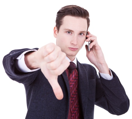 Business man with bad news on his cell phone disapproving  photo