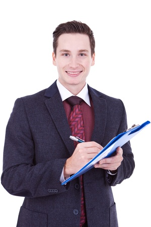 Business man with relaxed look writing on clipboard over white  photo