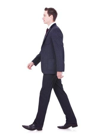 pasear: imagen de un hombre de negocios joven que camina hacia adelante - vista lateral