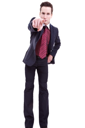 Portrait of an angry young business man in suit pointing at you isolated over white background  photo
