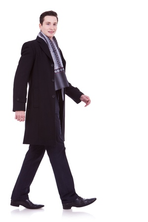 see side: side view of a walking business man, looking to the camera, on white background