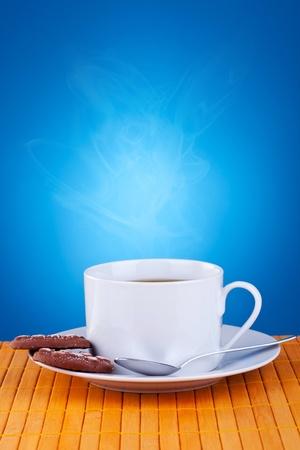 tarde de cafe: café fresco y galletas sobre fondo azul