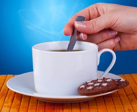 stir: hand of a woman stiring in a fresh cup of coffee on blue background.