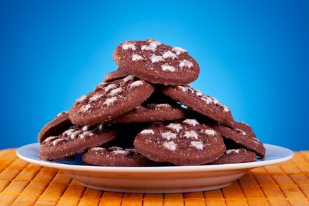 big pile of brown cookies on plate against blue background photo