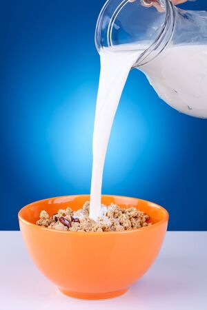 Healthy Breakfast-Cornflakes and Milk Splash on blue background photo