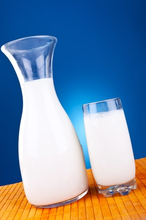 glass and jar of fresh cow milk on a white background photo